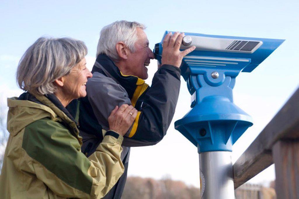 Senior couple, man looking through telescope, side view : Stock Photo