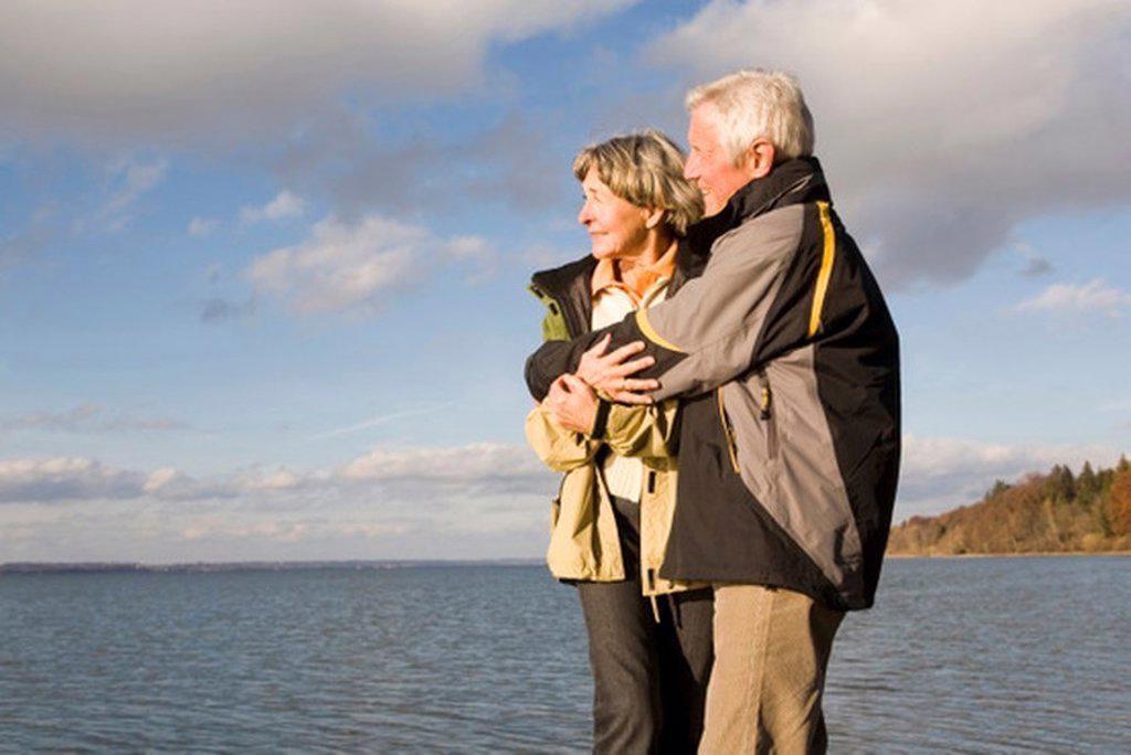 Senior couple embracing, side view : Stock Photo