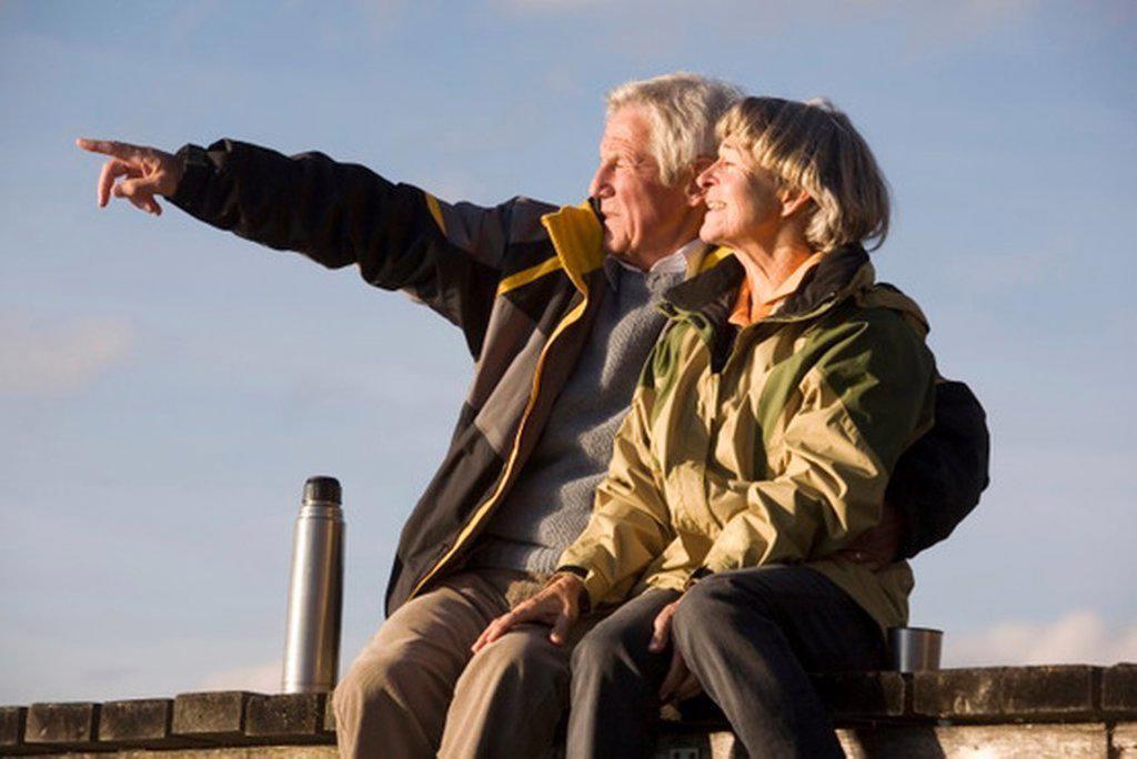 Senior couple sitting on jetty, man pointing : Stock Photo