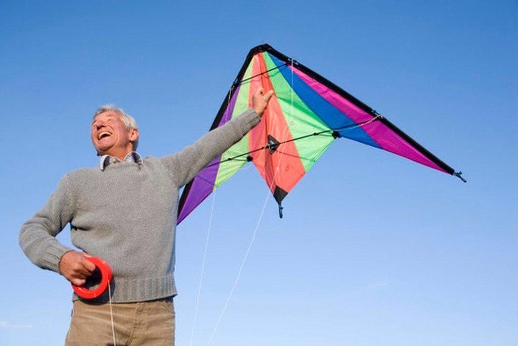 Senior man flying kite, smiling, low angle view : Stock Photo