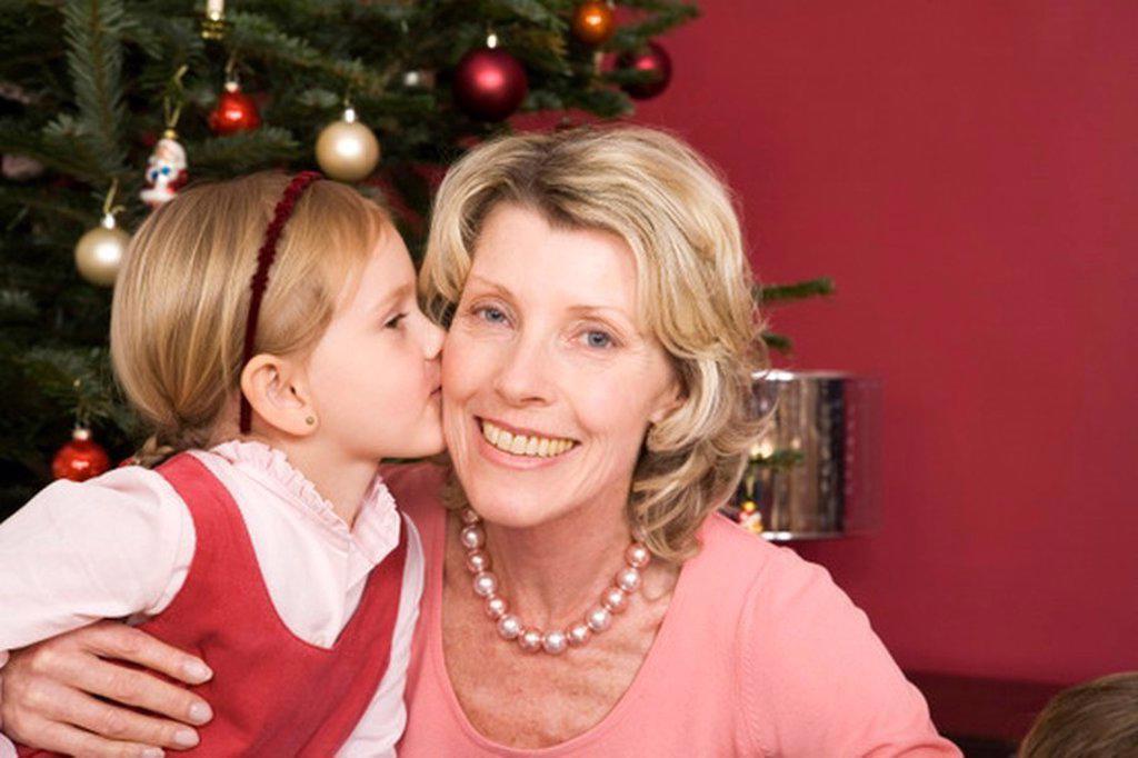 Little girl kissing grandmother on Christmas eve : Stock Photo