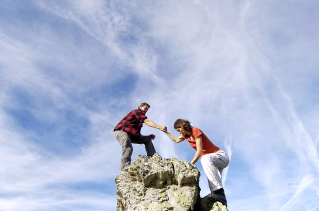 Couple climbing on summit : Stock Photo