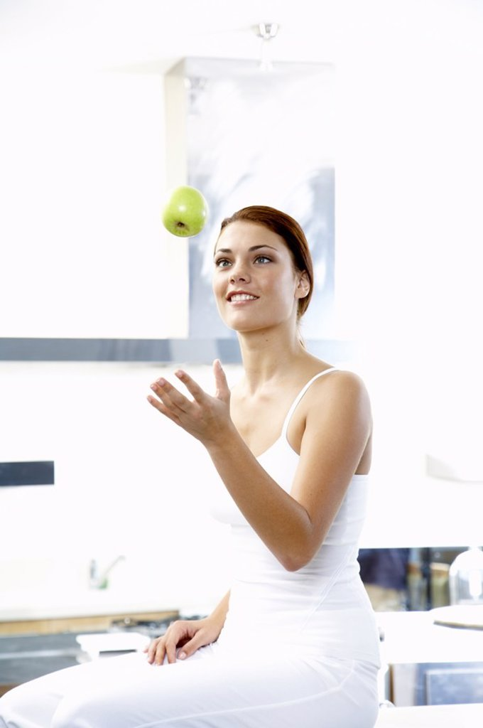 Youong woman throwing apple : Stock Photo