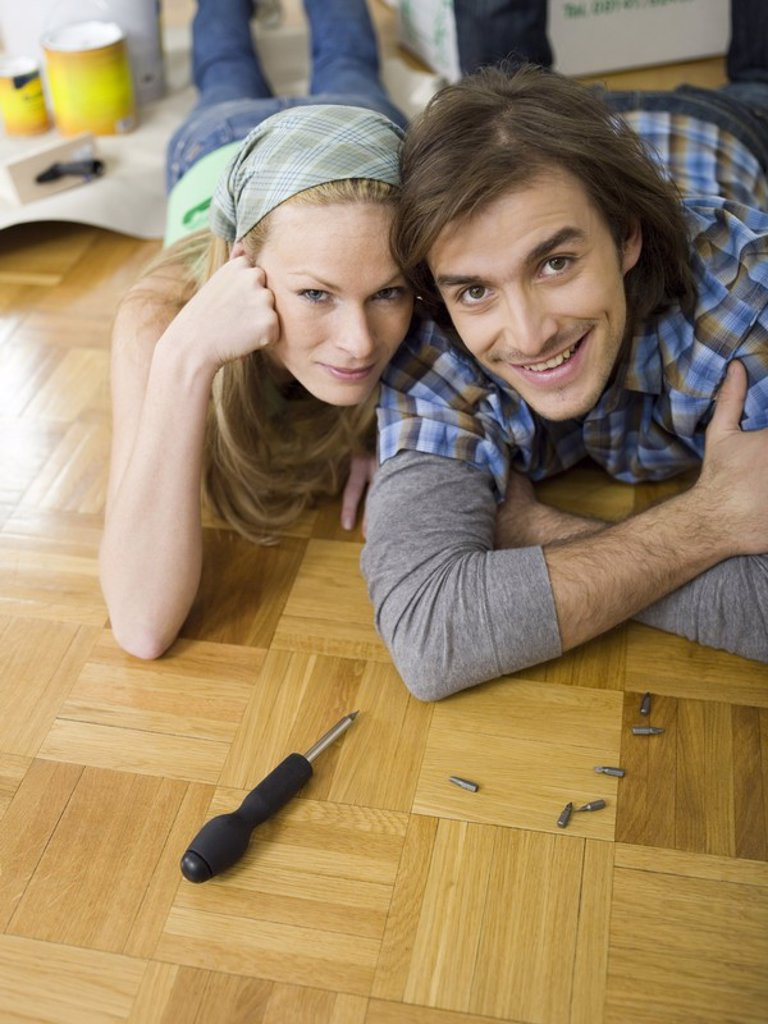 Couple lying on floor, looking to cmera : Stock Photo