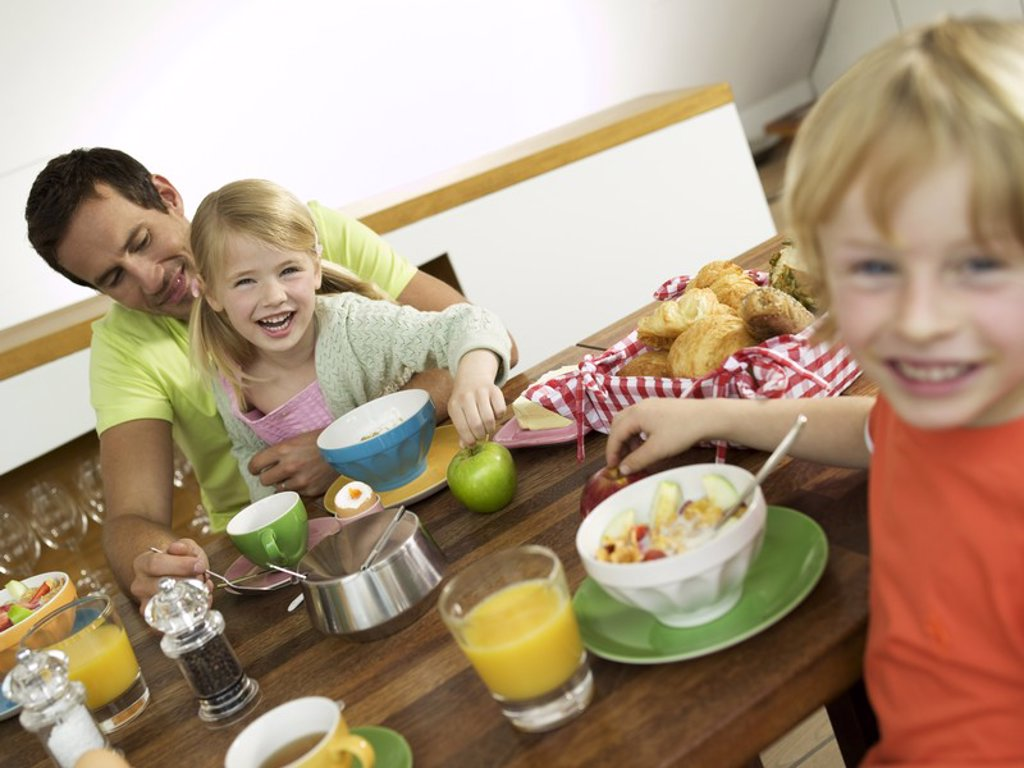 Stock Photo: 1815R-29360 Father and children at breakfast table