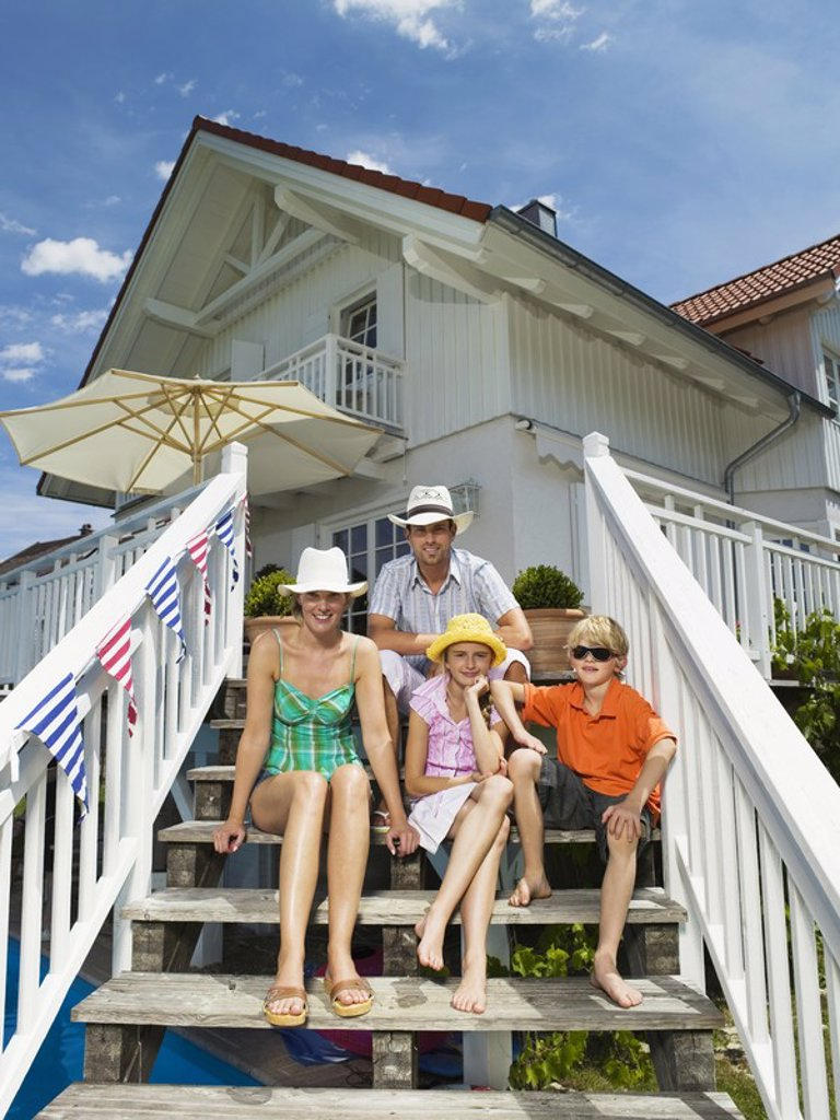 Stock Photo: 1815R-29474 Family sitting in front of house