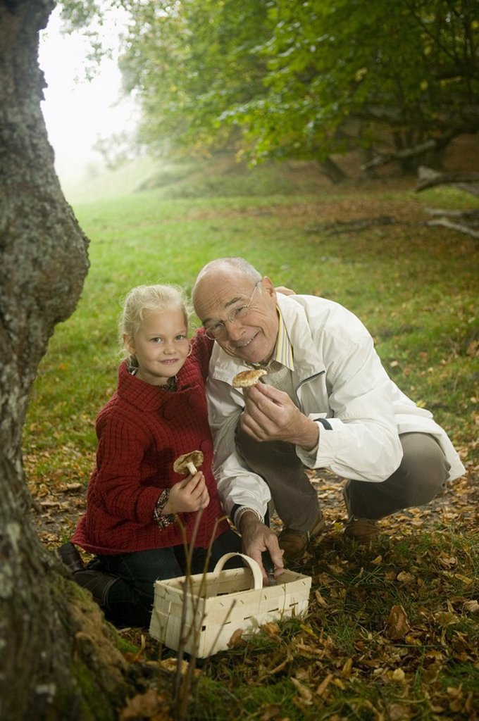 Germany, Baden-Württemberg, Swabian mountains, Grandfather and granddaughter searching mushrooms in the forest, portrait : Stock Photo