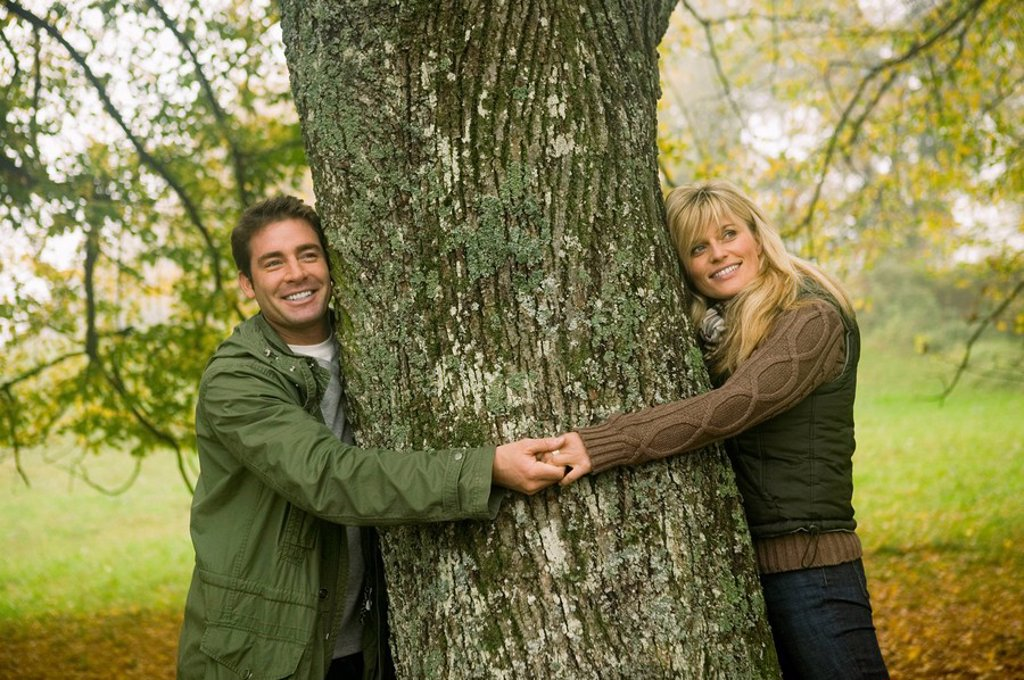 Germany, Baden-Württemberg, Swabian mountains, Couple smiling and hugging tree, portrait : Stock Photo