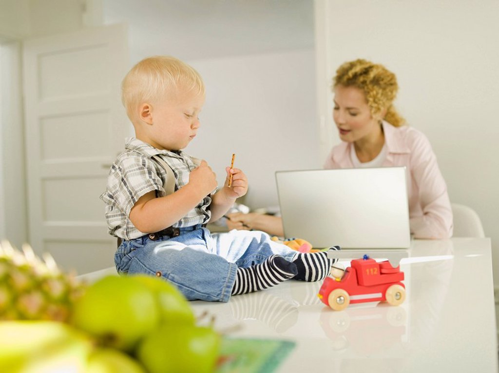 Mother and baby boy 12-24 months, mother using laptop : Stock Photo
