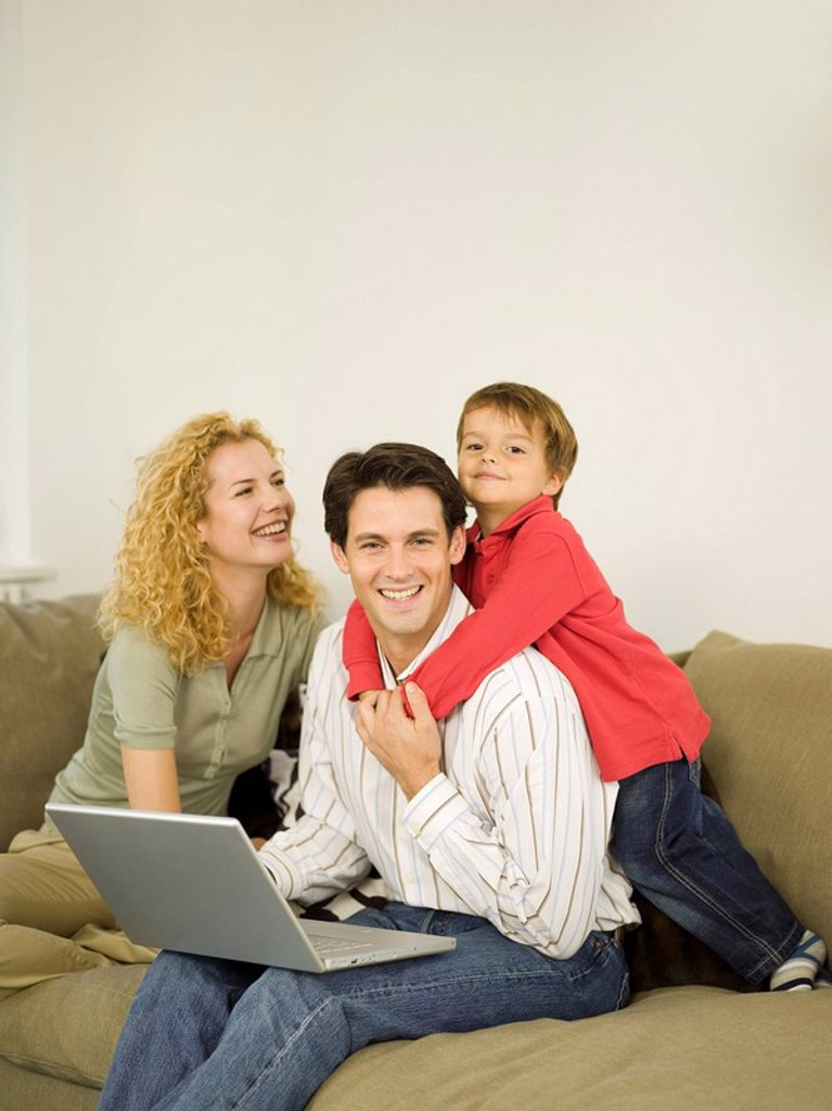 Stock Photo: 1815R-30072 Young family in living room, father using laptop