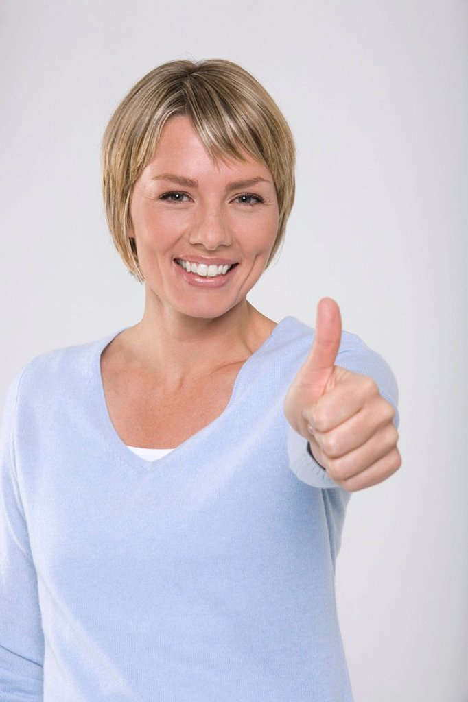 Stock Photo: 1815R-30146 Young woman making thumbs up gesture, smiling, portrait