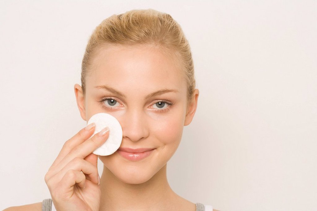 Young woman using cotton pad on face, portrait : Stock Photo