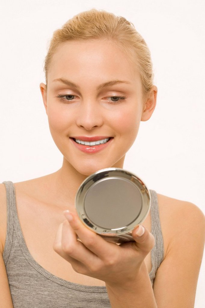 Woman looking at self in make-up mirror, portrait : Stock Photo