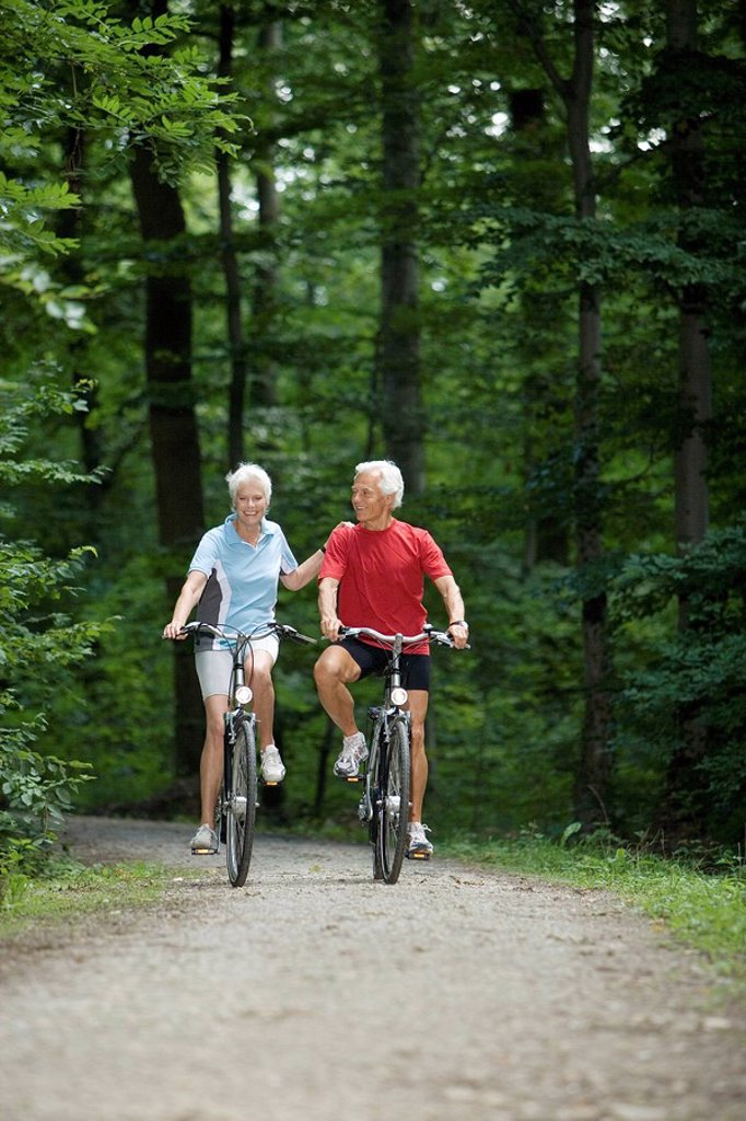 Senior couble biking on forest track : Stock Photo