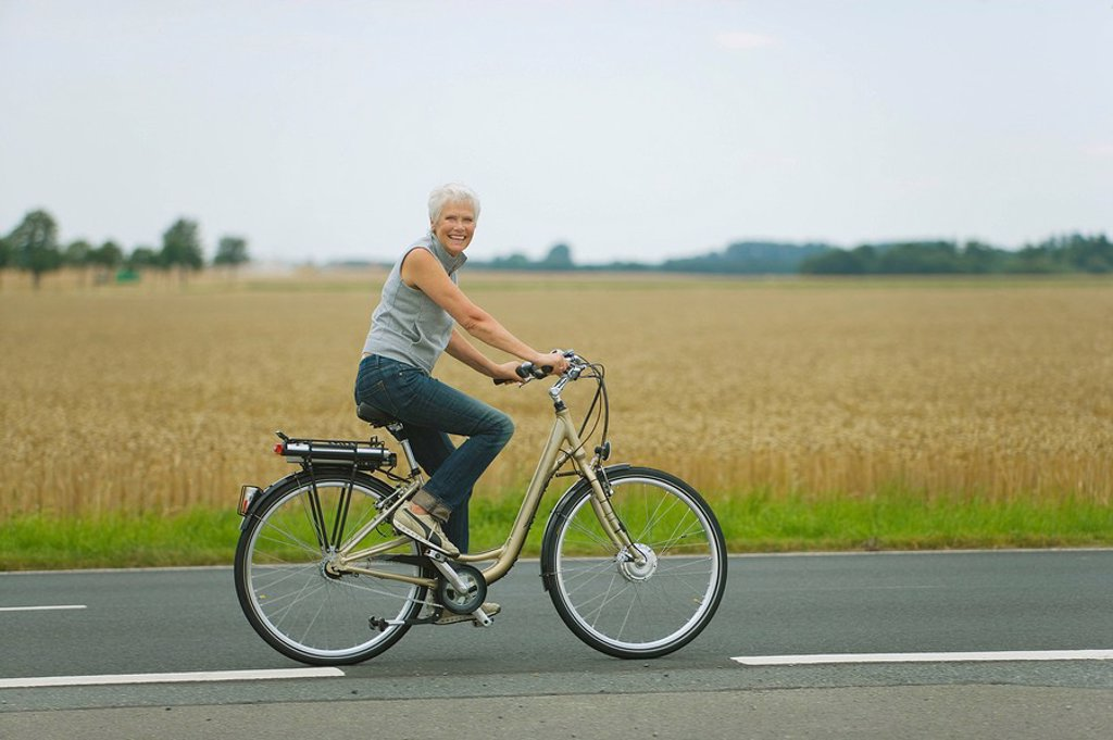 Senior woman biking on road : Stock Photo