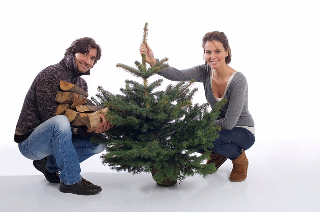 Stock Photo: 1815R-30624 Couple with Christmas tree and firewood