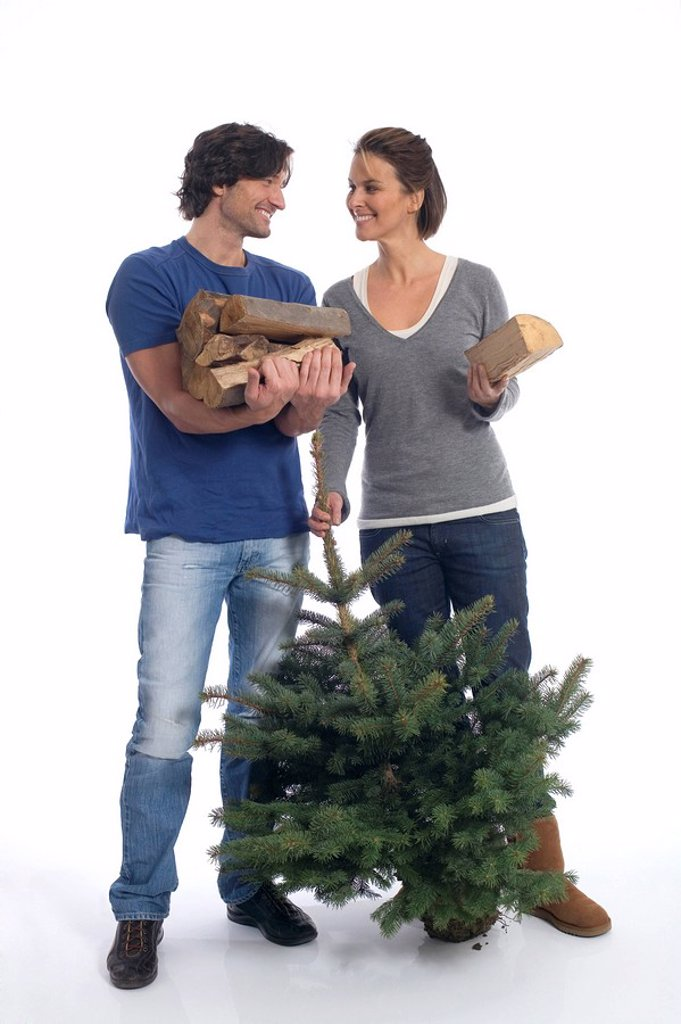 Couple with Christmas tree and firewood : Stock Photo