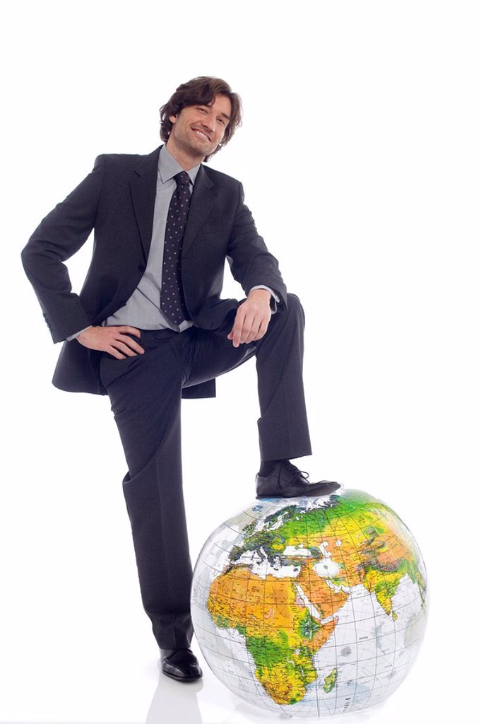 Businessman standing by globe : Stock Photo