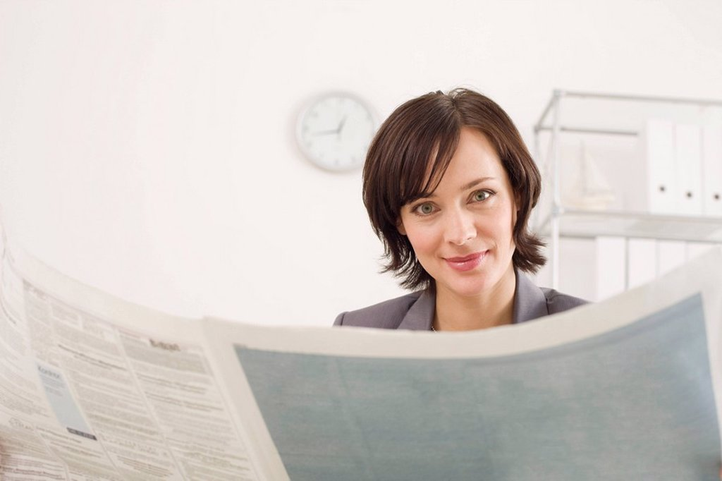 Businesswoman reading newspaper, portrait : Stock Photo