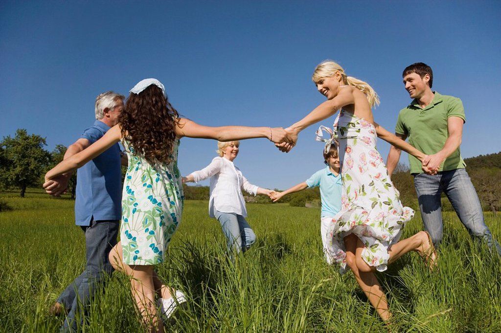 Stock Photo: 1815R-31536 Germany, Baden Württemberg, Tübingen, Three generation family dancing in meadow