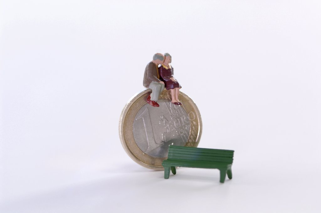 Figurines sitting on coin, bench aside : Stock Photo