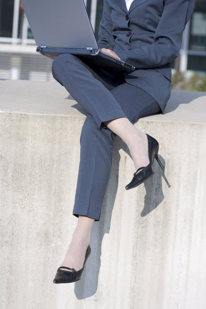 Business woman using laptop, low section : Stock Photo