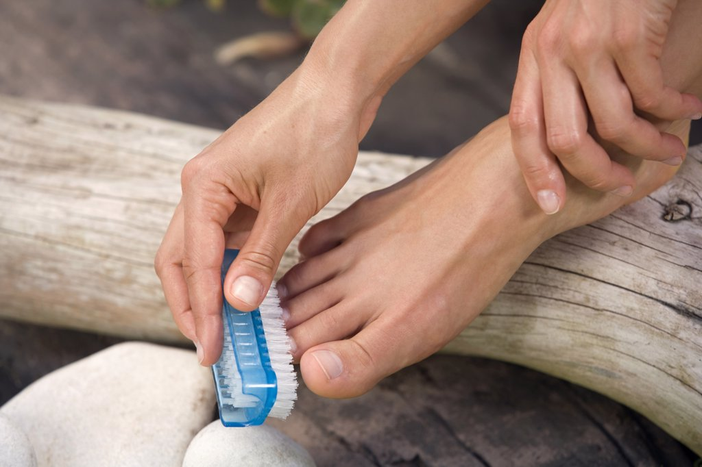 Woman brushing her feet, low section : Stock Photo