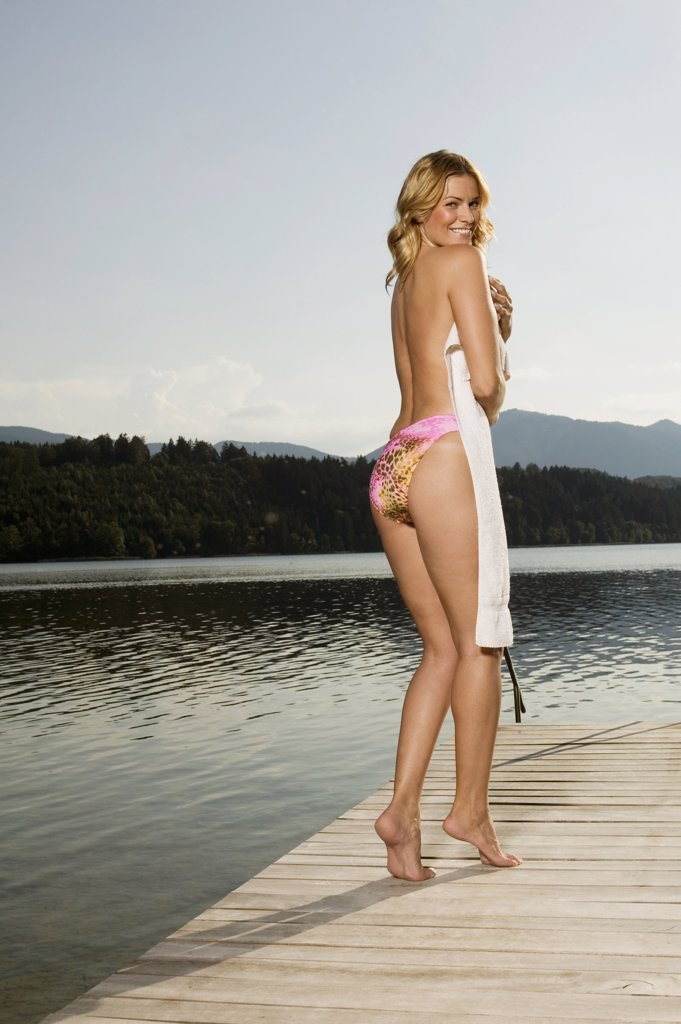 Woman standing onjetty, covering with towel, rear view : Stock Photo