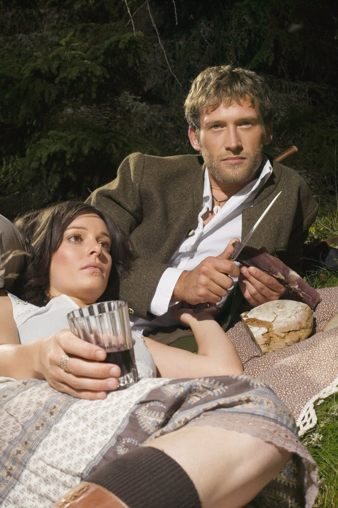 Stock Photo: 1815R-33472 Young couple lying in meadow, having picnic
