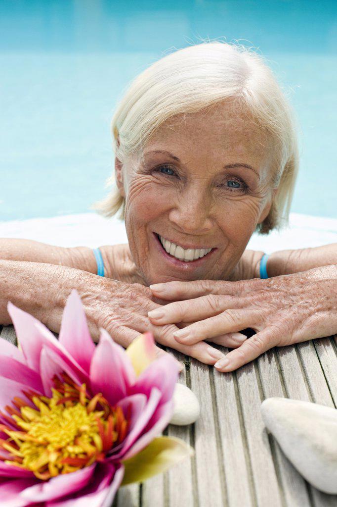 Stock Photo: 1815R-33647 Germany, Senior woman leaning on edge of pool, portrait
