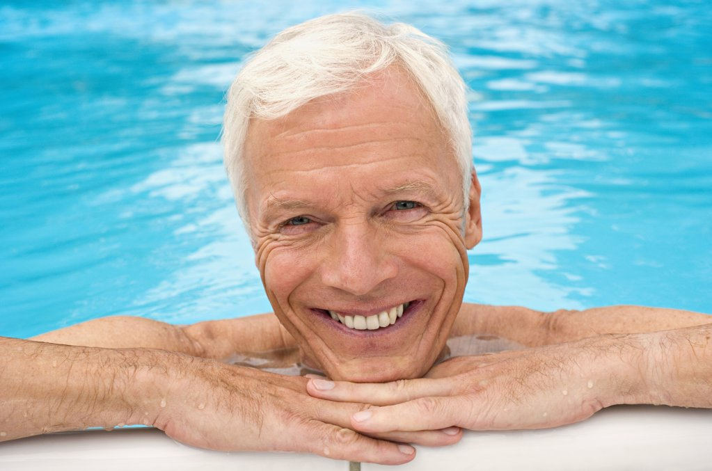 Stock Photo: 1815R-33651 Germany, senior man relaxing in pool, close-up, portrait