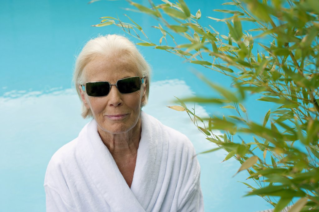 Germany, senior woman at pool, wearing sun glasses : Stock Photo