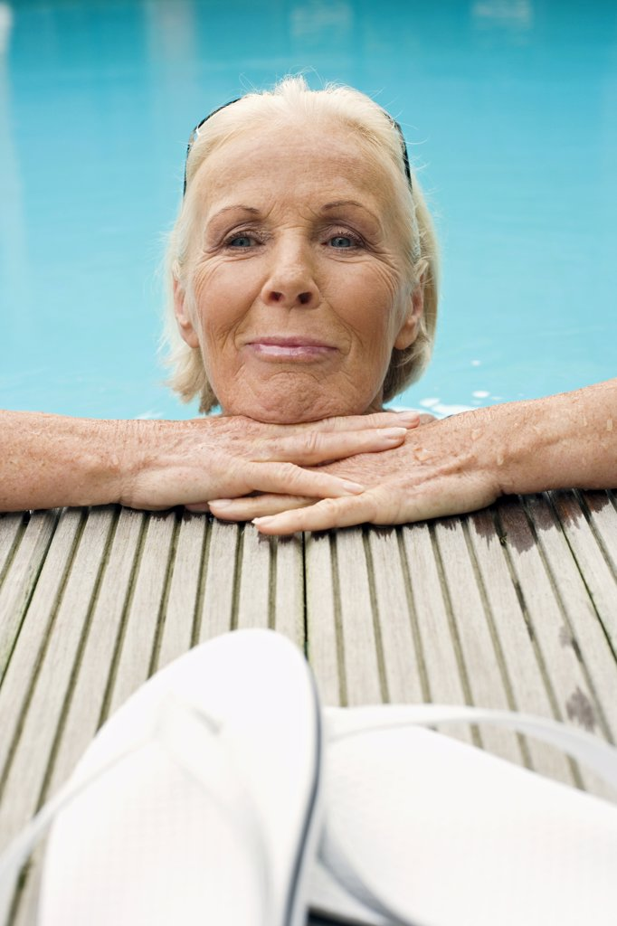 Stock Photo: 1815R-33672 Germany, Senior woman resting on edge of pool, smiling