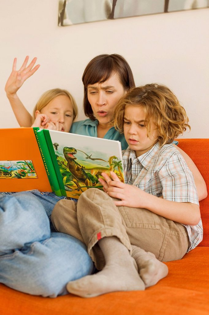 Stock Photo: 1815R-33859 Mother reading story book to children