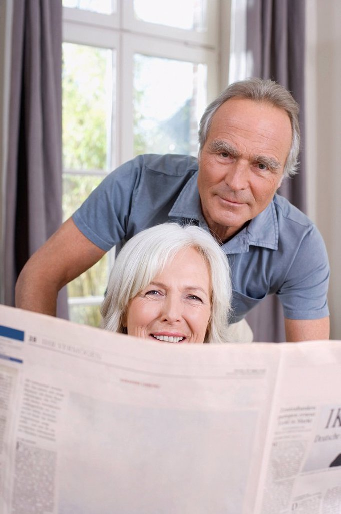 Senior Woman holding a newspaper, senior man behind, portrait : Stock Photo