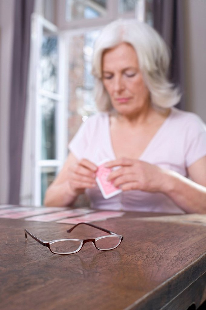 Senior woman playing Solitaire, portrait : Stock Photo