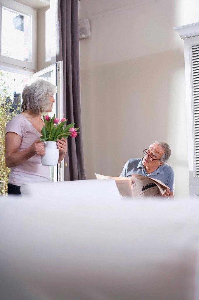 Senior woman holding flower vase, man reading newspaper : Stock Photo