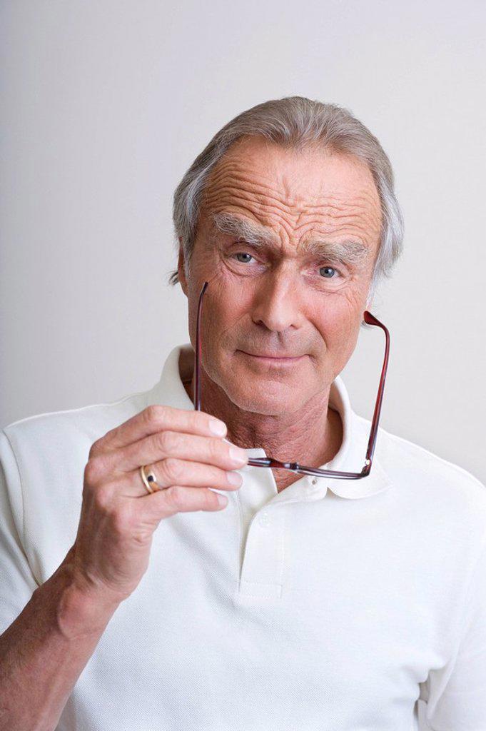 Senior man holding glasses, portrait : Stock Photo