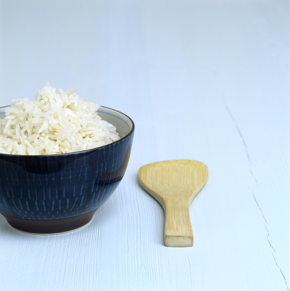 Cooked rice in a dish, wooden spoon aside : Stock Photo