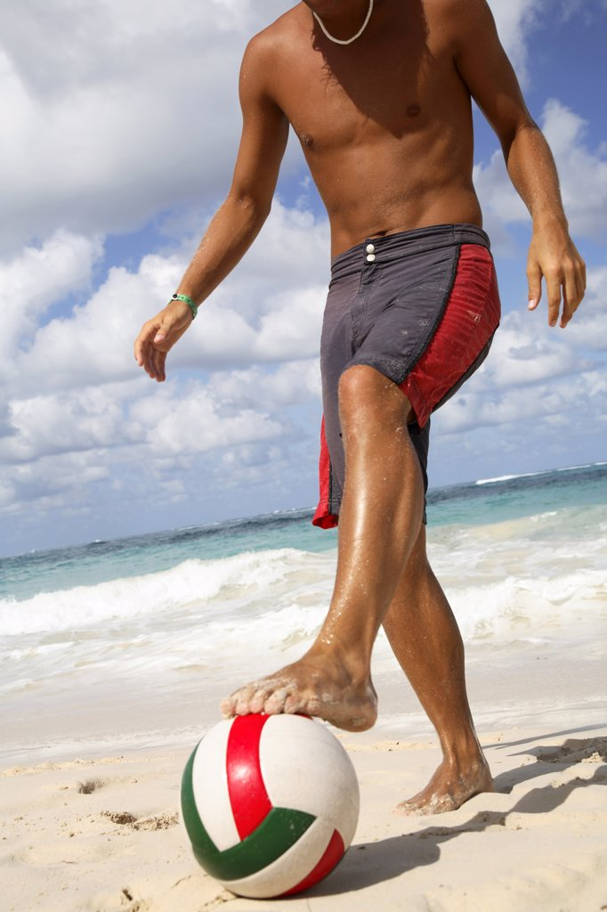 Stock Photo: 1815R-35228 Young man playing football on beach