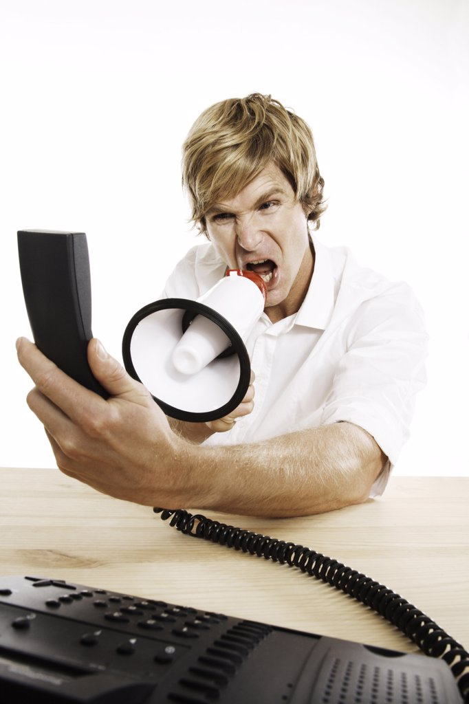 Stock Photo: 1815R-35298 Man holding phone, shouting in megaphone