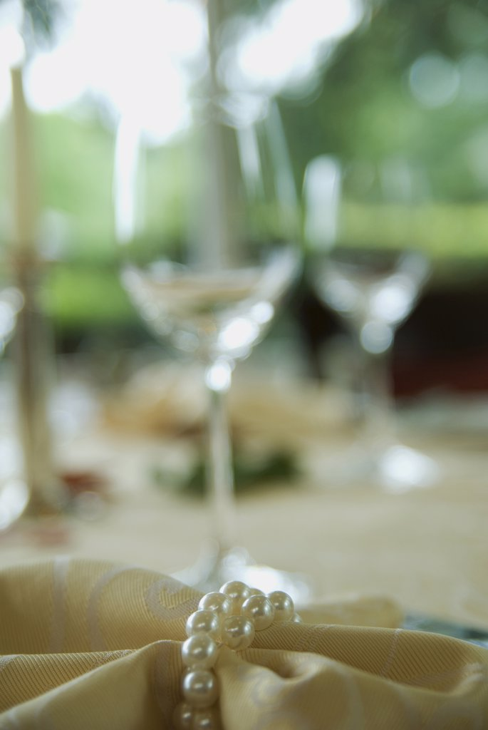 Napkin with pearls, wine glasses in the background : Stock Photo