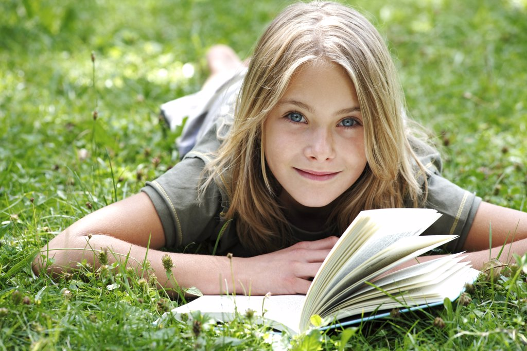 Stock Photo: 1815R-35859 Girl (13-14) lying on grass reading, smiling