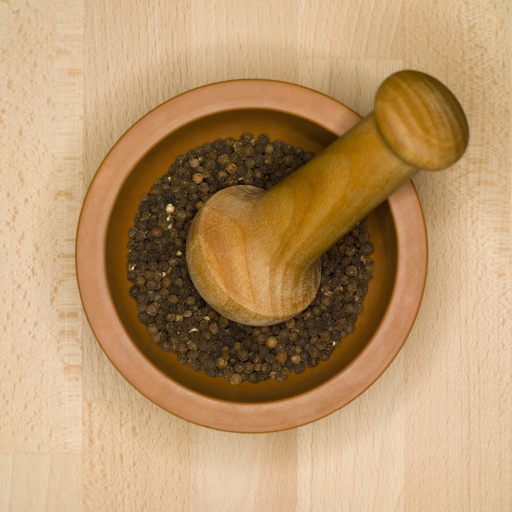 Peppercorns in mortar with pestle, elevated view : Stock Photo