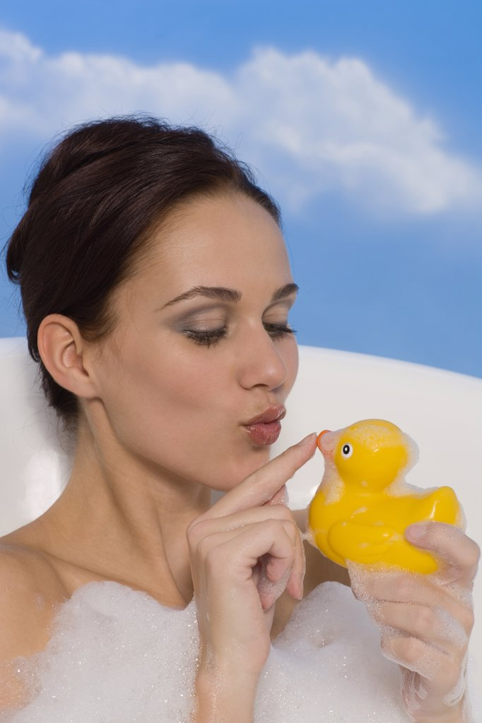 Stock Photo: 1815R-37203 Young woman in bath holding rubber Duck, portrait