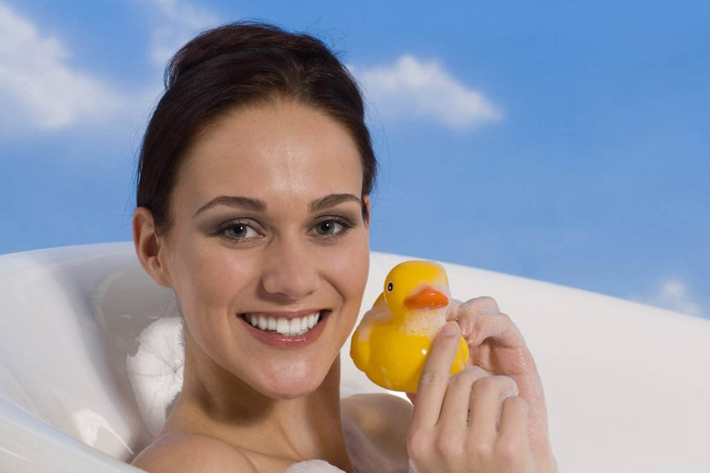 Stock Photo: 1815R-37204 Young woman in bath holding rubber Duck, portrait