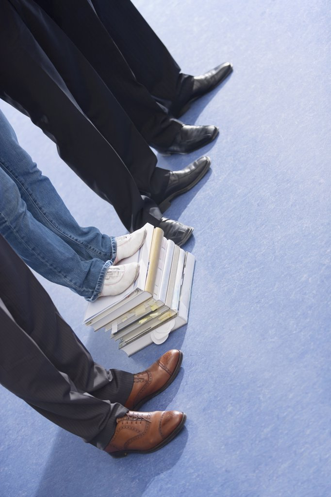 Four persons, one standing on stack of books, low section : Stock Photo