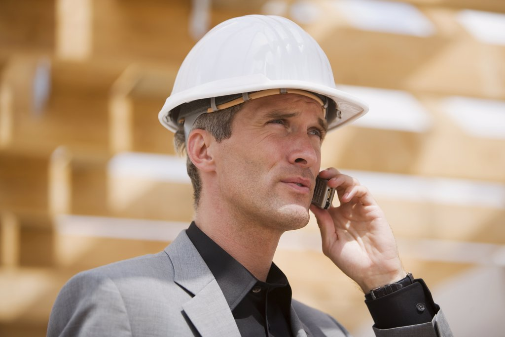 Man with hardhat talking on mobile phone : Stock Photo