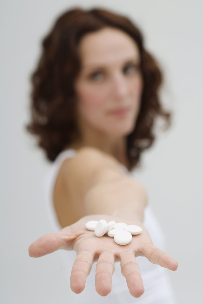 Woman holding tablets on hand, close up : Stock Photo