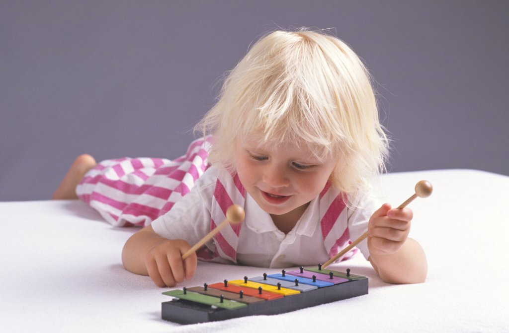 little child trying to play xylophone : Stock Photo